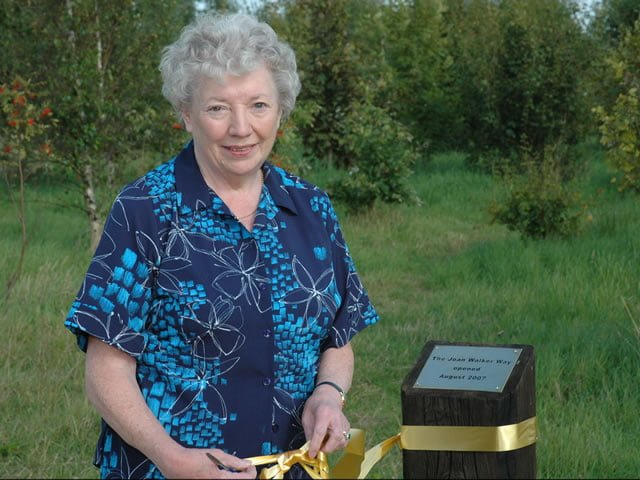 Joan Walker cutting the ribbon to open the woodland
