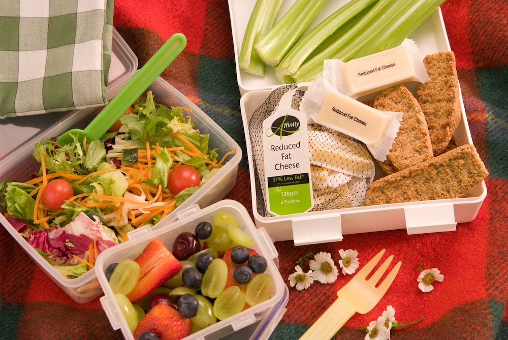 Snacking cheese in a lunch box with salad, bread and fruits