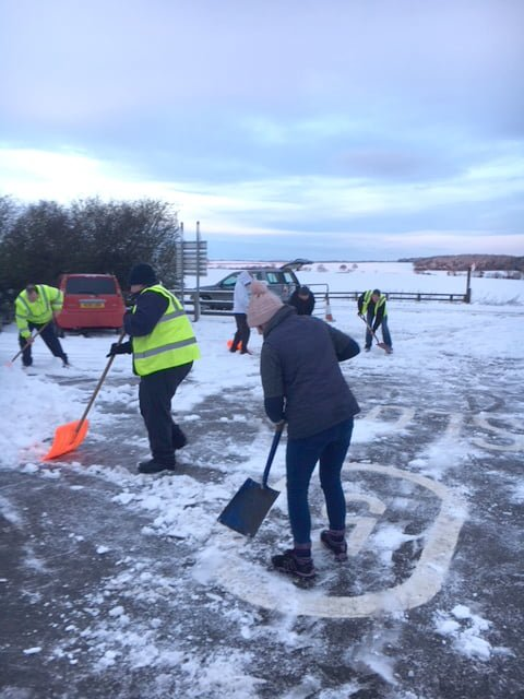 Staff shovelling snow in the entrance to the site
