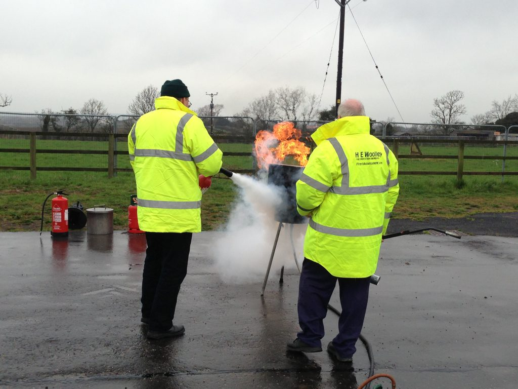 Two people using a fire extinguisher to put out a demonstration fire